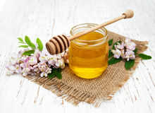 Honey with acacia blossoms. On a wooden background stock image