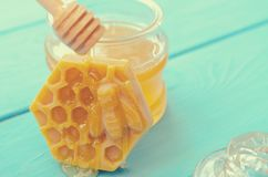 Honey and honey accessories for its use on a blue wooden background. royalty free stock images