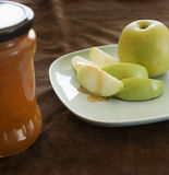 Honey and apple. Honey dripping on a green apple slice with jar Royalty Free Stock Image