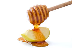 Honey and apple. Honey drippin on a green apple slice isolated on white stock images