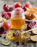 Honey, apple, pomegranate and bread hala, table set with traditional food for Jewish New Year Holiday, Rosh Hashana. Honey, apple, pomegranate and hala, table stock photography