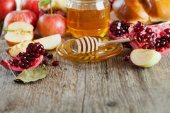 Honey, apple, pomegranate and bread hala, table set with traditional food for Jewish New Year Holiday, Rosh Hashana Stock Photo