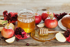 Honey, apple, pomegranate and bread hala, table set with traditional food for Jewish New Year Holiday, Rosh Hashana. Honey, apple, pomegranate and hala, table Stock Images