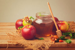 Honey, apple and pomegranate on wooden table. Retro filter effect Royalty Free Stock Photo