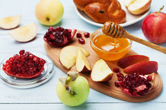 Honey,apple slices,pomegranate and hala on wooden board. Table set with traditional food for Jewish New Year Holiday,Rosh Hashana. Stock Photography