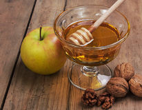 Honey, apple and walnuts. On wooden table Royalty Free Stock Image