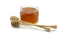 Honey. Bank of honey and wooden spoon for honey are isolated on a white background Royalty Free Stock Photos
