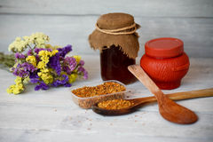 Honey and bee pollen on a wooden background. Honey and bee pollen on a white wooden background royalty free stock image
