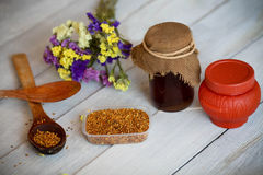 Honey and bee pollen on a wooden background. Honey and bee pollen on a white wooden background royalty free stock photography