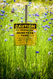 Honey Bee yard warning sign. Posted sign lets all know to watch out for Honey Bees that are flying around the flowers Stock Photos