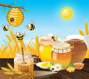 Honey bees landscape. Bee cocoon on a branch next to which bees are flying. Wooden table on which a vessel with honey. Summer landscape of wheat fields and sky Stock Photos