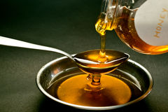 Honey. Being poured out on spoon Stock Images