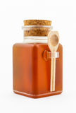 Honey Bottle with Cork Cap and Wood Spoon Royalty Free Stock Photo