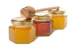 Honey in bottles and wooden dipper Stock Image