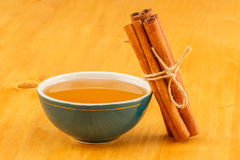 Honey in bowl and cinnamon. Honey in green porcelain bowl and cinnamon sticks on wooden tabletop surface royalty free stock image
