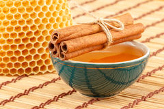 Honey in bowl with honeycomb and cinnamon. Honey in green porcelain bowl, with honeycomb and cinnamon sticks on light rustic mat Royalty Free Stock Photos