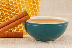 Honey in bowl with honeycomb and cinnamon. Honey in green porcelain bowl, with honeycomb and cinnamon sticks on rustic table cloth stock photography