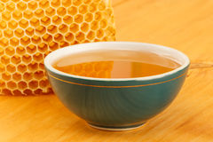 Honey in bowl with honeycomb and cinnamon. Honey in green porcelain bowl, with honeycomb on wooden tabletop surface Stock Photos