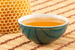 Honey in bowl with honeycomb. Honey in green porcelain bowl, with honeycomb on light rustic mat royalty free stock images