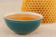 Honey in bowl with honeycomb. Honey in green porcelain bowl, with honeycomb on rustic table cloth Royalty Free Stock Photos