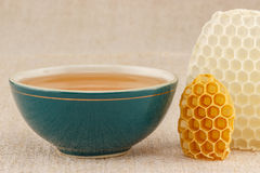 Honey in bowl with honeycomb. Honey in green porcelain bowl, with honeycomb on rustic table cloth stock photo