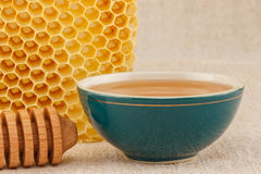 Honey in bowl with honeycomb. Honey in green porcelain bowl, with honeycomb and wooden dipper on rustic table cloth stock image