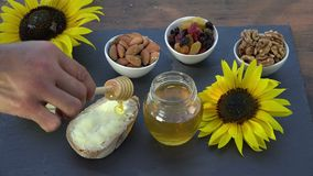 Honey, bread, butter and dried fruit. Honey is deposited on the slice stock video footage