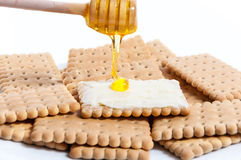 Honey and butter on classics crackers. Put honey and butter on classics crackers isolated on white background stock image