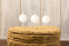 Honey cake with candles on a set background. Royalty Free Stock Photos