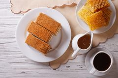 Honey cake, coffee, and a honeycomb. horizontal top view Stock Image