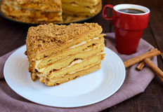 Honey cake and cup of coffee  on a dark wooden background. Cutting a piece Stock Photography