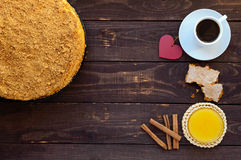 Honey cake and cup of coffee  on a dark wooden background. Stock Photos