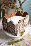 Honey cake decorated with gingerbread houses. Rustic style, selective focus. Royalty Free Stock Images