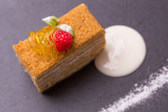 Honey cake. Decorated with raspberry on stone plate Stock Photography