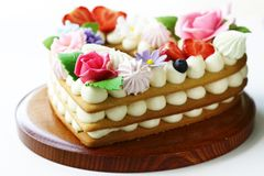 Honey cake with mascarpone cream. And decorated with flowers stock photography