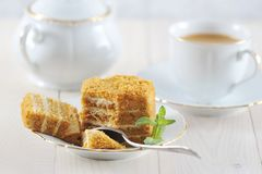 Honey cake and a mint leaf on the saucer. With a Golden rim - light on wooden background Stock Image