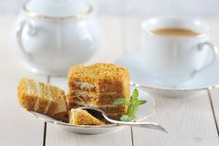 Honey cake and a mint leaf on the saucer. With a Golden rim - light on wooden background Stock Photos