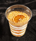 Honey cake in plastic cup on black background Royalty Free Stock Photography