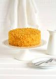 Honey cake on a stand, white plates and white enamel jug Stock Photo