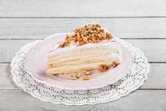 Honey cake with walnuts on plate, on a light wooden background Royalty Free Stock Photo