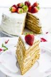 Honey cake. With white cream and strawberries Royalty Free Stock Photo