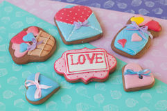Honey cakes with glazed hearts and word love lay on different color background Royalty Free Stock Photo