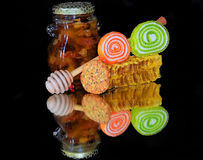 Honey with candy Stock Images