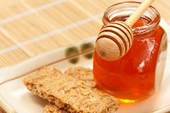 Honey with cereal butter and wood dipper Royalty Free Stock Images