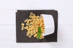 Honey cereal rings. Bowl of honey cereal rings spilt out on grey place mat stock photos