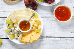 Honey and cheeses on a white plate Stock Photo