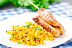 Honey chicken skewers with grilled corn salad Stock Image