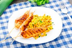 Honey chicken skewers with grilled corn salad Stock Photography