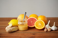 Honey, citrus fruits, ginger and garlic on wood Stock Photography
