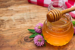 Honey and clover flowers. Honey pot on a wooden table stock images